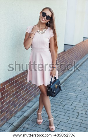 Happy beautiful young girl in a pink dress with a black bag near the wall