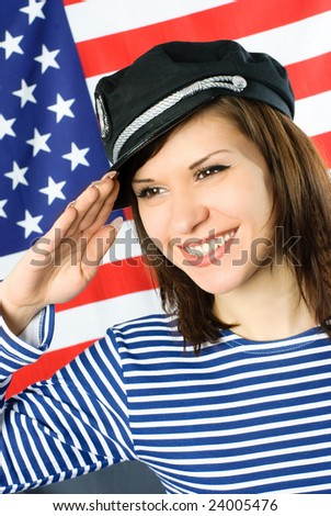 happy beautiful young sailor stands near the American flag and salutes - stock photo