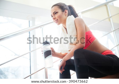 Happy beautiful young sportswoman resting and drinking water on stairs in gym  - stock photo