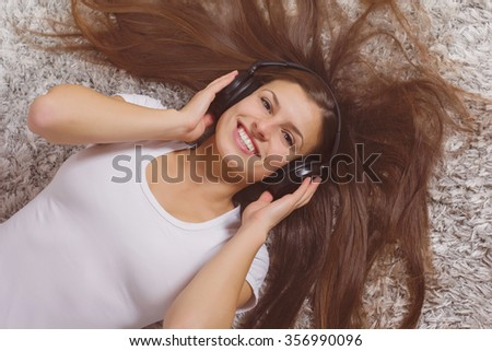 Happy Beautiful Young Woman, enjoyment in music on headphones at home
