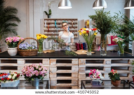 Happy beautiful young woman florist in glasses standing in flower shop - stock photo