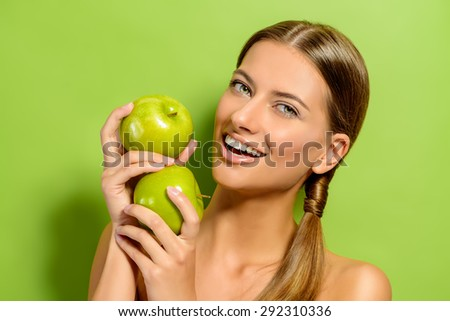 Happy beautiful young woman holding fresh apples over green background. Healthy lifestyle. Healthy eating. Fruits and vegetables.