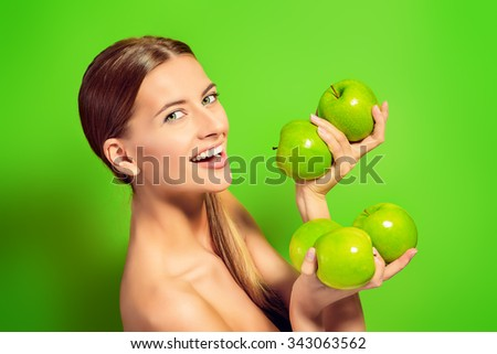 Happy beautiful young woman holding fresh apples over green background. Healthy lifestyle. Healthy eating. Fruits and vegetables.  - stock photo