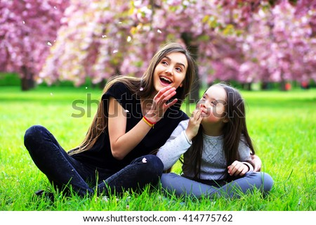 Happy beautiful young woman in blossom park with trees and flowers. - stock photo