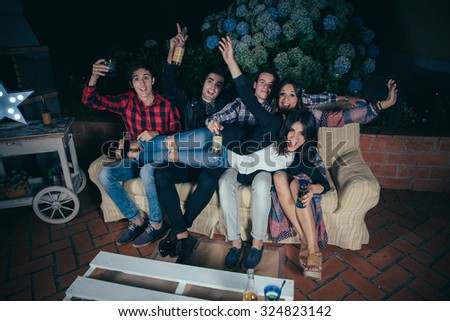 Happy beautiful young woman lying over her group of friends sitting in a sofa and holding drinks in a outdoors party. Friendship and celebrations concept.
