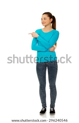 Happy beautiful young woman pointing aside. - stock photo