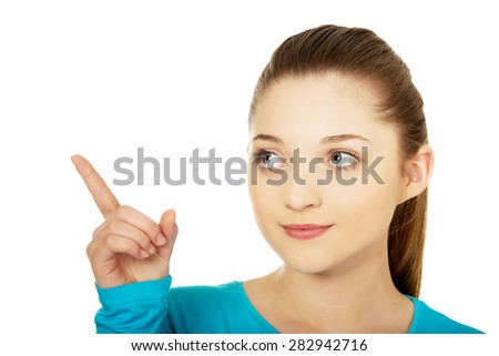 Happy beautiful young woman pointing up. - stock photo