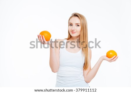 Happy beautiful young woman standing and holding two oranges over white background