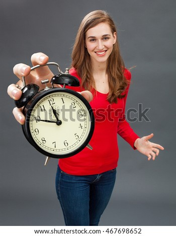 happy beautiful young woman standing with an alarm clock in her oversized hand for focus on patience and time management in the foreground