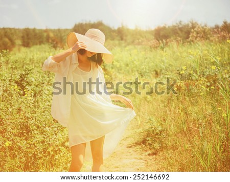 Happy beautiful young woman walking in summer park. Image with sunlight effect - stock photo
