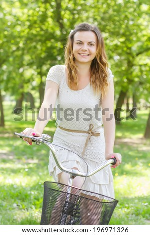 Happy beautiful young woman with bicycle in the park.