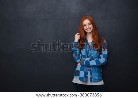Happy beautiful young woman with long red hair standing over blackboard background - stock photo