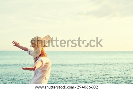 Happy beauty woman in hat is back opened his hands, relaxes and enjoys the sunset over the sea on the beach - stock photo