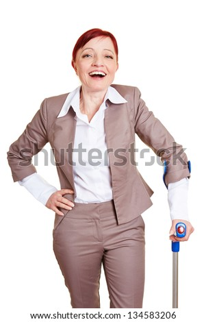 Happy best ager business woman standing with crutches - stock photo
