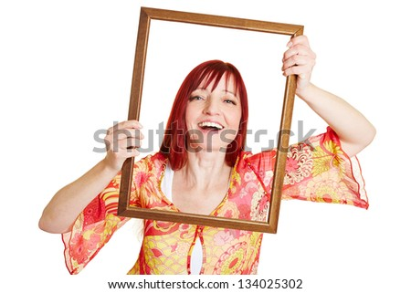 Happy best ager woman holding empty picture frame in front of her face - stock photo