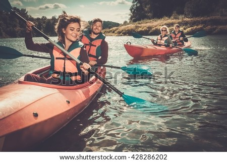 Happy best friends having fun on a kayaks - stock photo