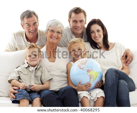 Happy big family on sofa holding a terrestrial globe - stock photo