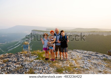 Happy big family travel together on top, peak of mountain. Traveler man and woman, father and mother with children on vacation. Beautiful nature landscape tourism, hiking. Parents with kids outdoors.