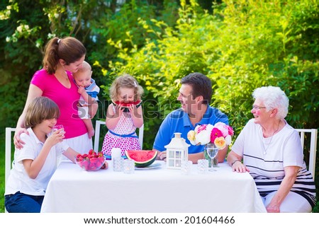 Happy big family - young mother and father with kids, teen age son, cute toddler daughter and a little baby, enjoying lunch with grandmother eating fruit, watermelon and strawberry in the garden  - stock photo
