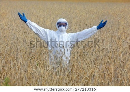 Happy biotechnology engineer in white uniform, mask, goggles on field of crops  - stock photo