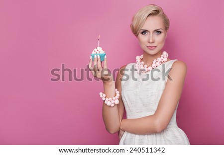 Happy Birthday. Beautiful young women holding small cake with colorful candle. Studio portrait over pink background - stock photo