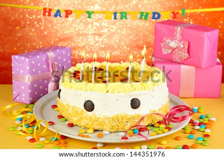 Happy birthday cake and gifts, on red background - stock photo