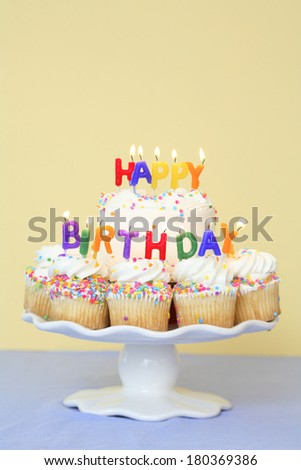 Happy Birthday cupcakes with candles on stand and blue and yellow background - stock photo