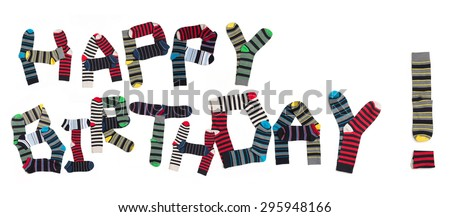 Happy birthday expression made from socks. Multicoloured socks are organized in two lines isolated on white background. - stock photo
