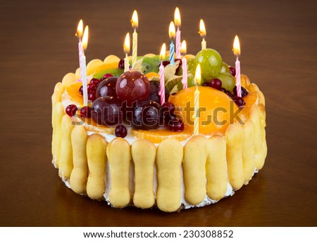 Happy birthday fruit cake with candles on wooden table background - stock photo
