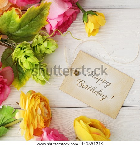 happy birthday greeting card. Gift tag and flowers on white wooden background - stock photo