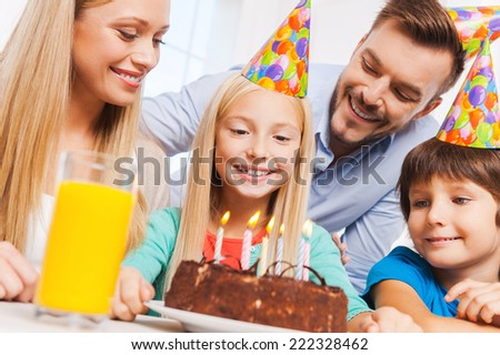 Happy birthday! Happy family of four celebrating birthday of happy little girl sitting at the table with birthday cake on it  - stock photo