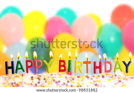 Happy birthday lit candles on colorful balloons background - stock photo