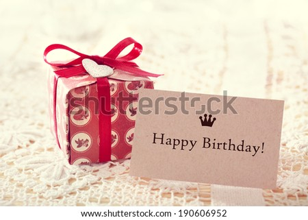 Happy birthday message written on a card with a hand crafted present box  - stock photo