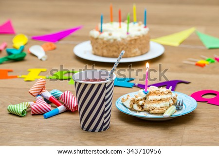 Happy birthday party still life with various garlands and objects, including a plate with cake and a candle and a paper cup with lemonade on a wooden surface - stock photo