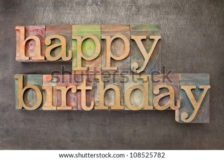 happy birthday - text in vintage letterpress printing blocks against a grunge metal sheet - stock photo