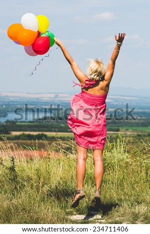 Happy birthday woman against the sky with rainbow-colored air balloons in hands - stock photo