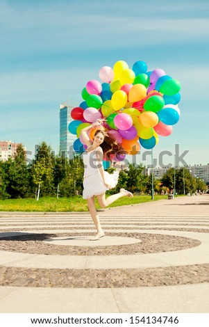 Happy birthday woman against the sky with rainbow-colored air balloons in her hands. sunny and positive energy of urban street. Young beautiful girl on the grass in the city.