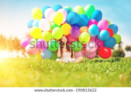Happy birthday woman against the sky with rainbow-colored air balloons in her hands. sunny and positive energy of nature. Young beautiful girl on the grass in the park. - stock photo