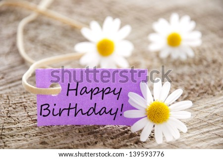 happy birthday written on a purple banner, flowery background - stock photo