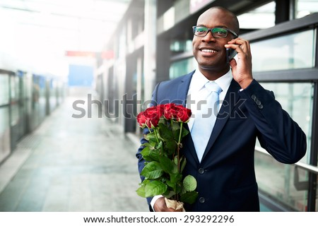 Happy Black American Businessman Holding Red Rose Flowers While Calling his Date on his Mobile Phone at the Metro. - stock photo