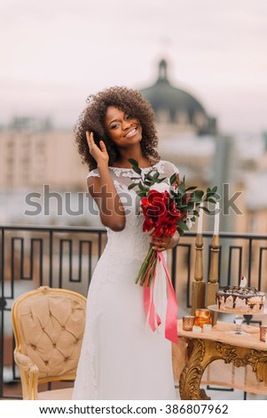 Happy black bride corrects her hair and smiling. Wedding day - stock photo