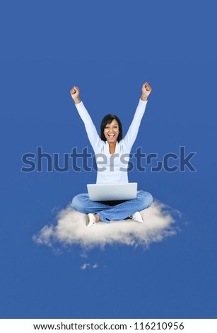 Happy black woman with computer sitting on cloud - stock photo