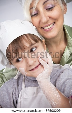 Happy, blond caucasian mother and daughter coocking - stock photo