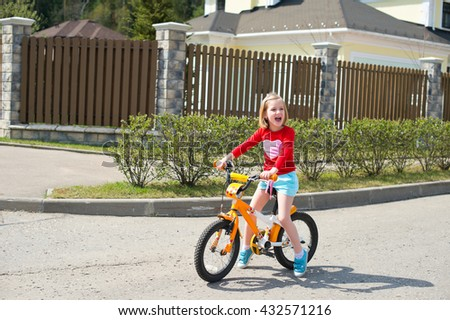 Happy blond child girl learning how to ride bicycle near house in village - stock photo