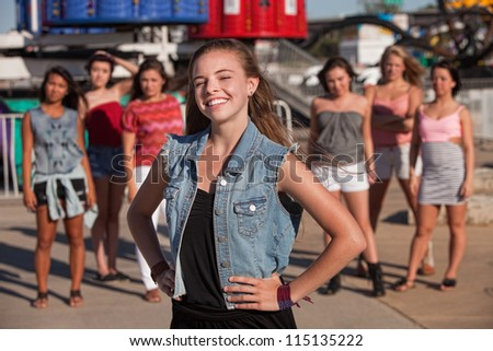 Happy blond teen with big smile in front of friends - stock photo