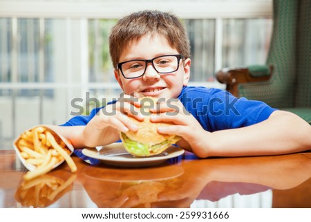 Happy blond tween enjoying a hamburger and french fries at home - stock photo