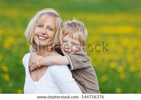 happy blond woman carrying her son against grassy field - stock photo