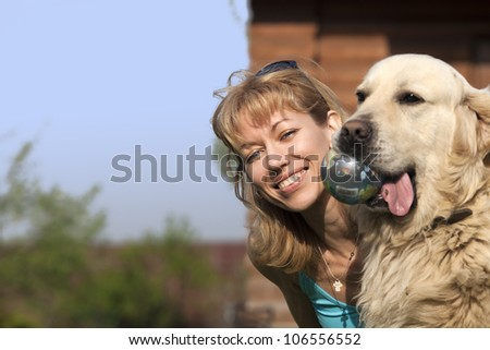 happy blond woman is playing with a dog