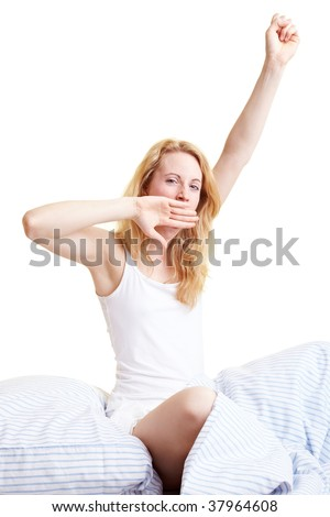 Happy blond woman sitting in her bed - stock photo