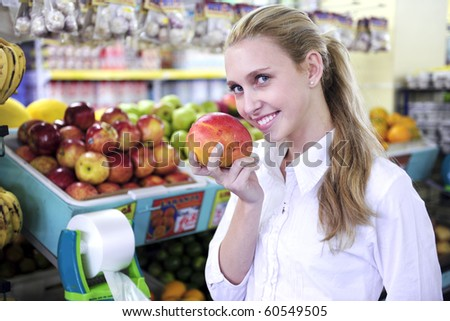 Happy blond woman smelling a mango in the supermarket - stock photo